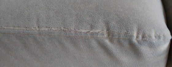 Poškozená látka ENOA CARABU v oblasti švů